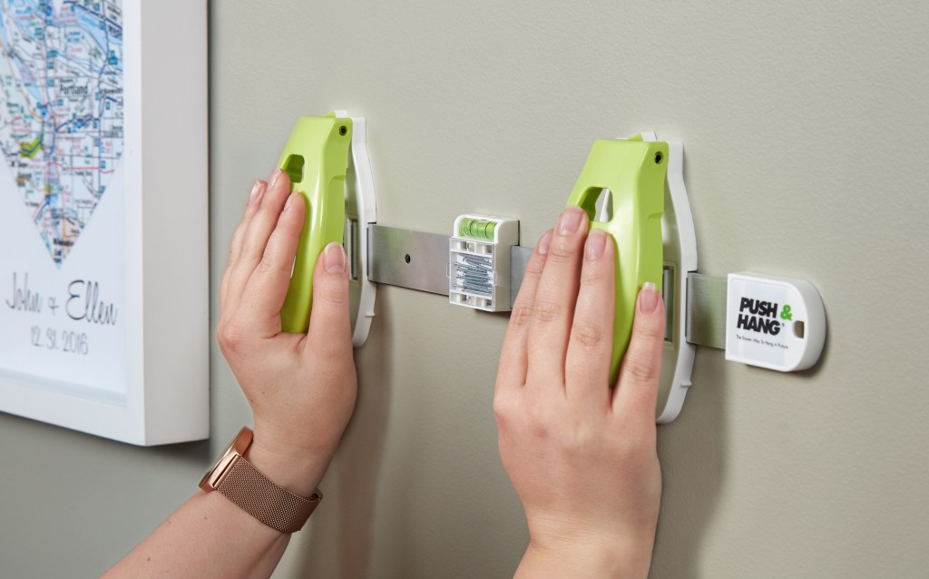 A woman is seen using Hangman Products' push & hang picture tool to easily put nails into a wall