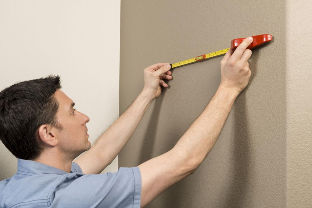 A man is seen using Hang-O-Matic's handheld ruler & level to measure the distance between two nails on a wall