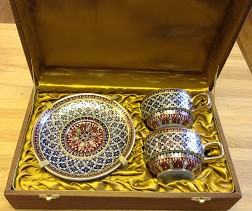 Beautiful, handpainted porcelain teacups and saucers nestle in famous Thai silk.
