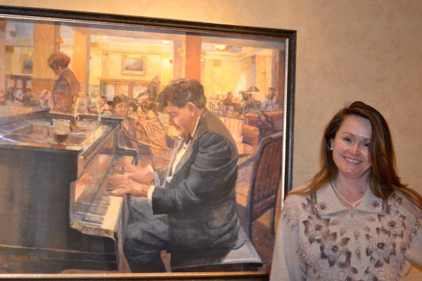 Natalia, proudly standing next to her likeness in Katie Musolff's painting of Dr. Hollander