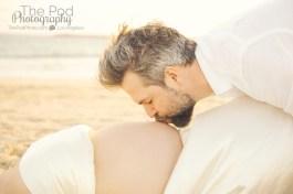 dad-kissing-pregnancy-belly-on-beach