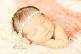 diamond-headband-on-sleeping-infant-pink-and-cream-colors