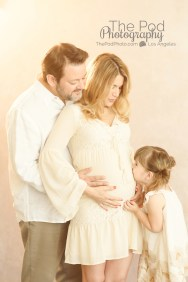 little-girl-kissing-moms-pregnancy-belly-in-studio-professional-photograph