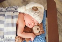 newborn-cuddling-bear-in-bed