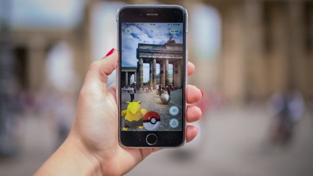 A-woman-points-her-smartphone-at-the-Brandenburg-Gate-as-she-plays-the-Pokemon-Go-mobile-game-in-Berlin-on-July-13-2016.-AFP-dpa-Sophia-Kembowski