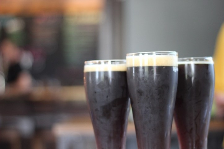 three beers in glasses sitting on a bar