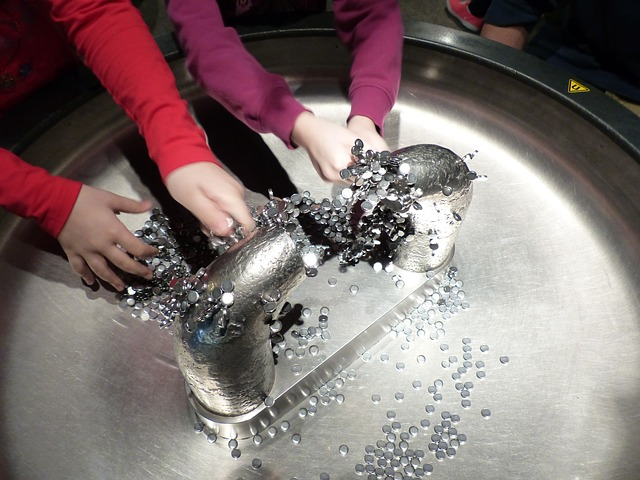a magnet exhibit at a museum with two kids hands reaching in to play.