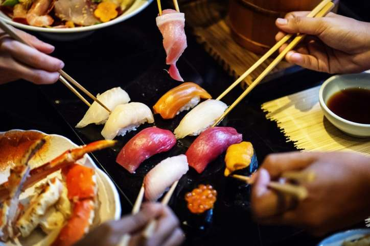 Four friends with chopsticks reaching for sushi.