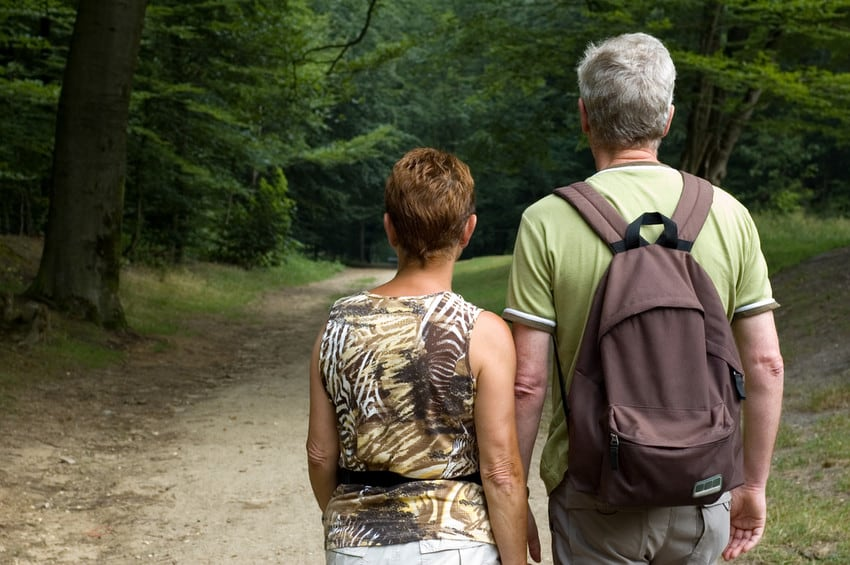 An older couple hiking along a trail in the woods.
