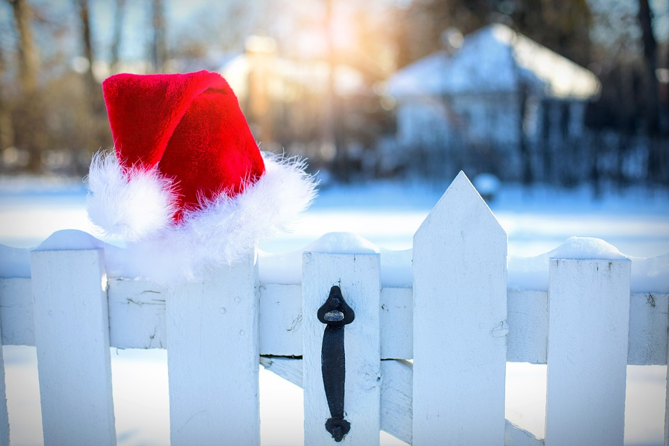 A Santa hat sitting on a white picket fence.