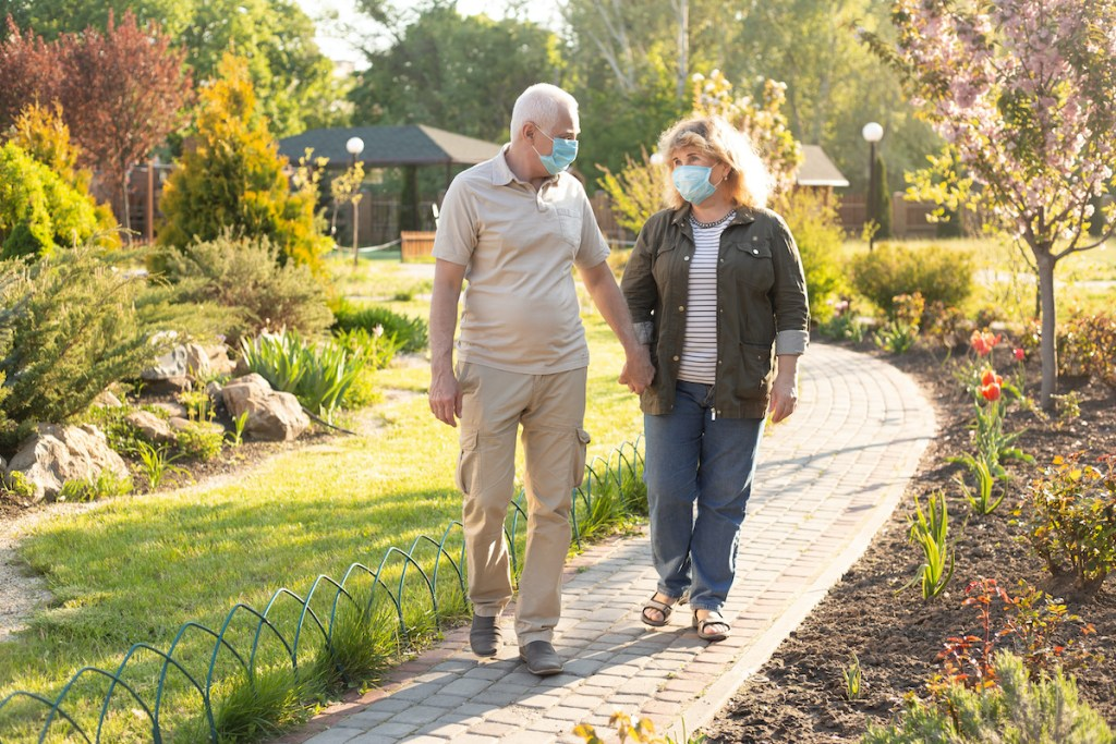 Older adults with masks walking to the clubhouse