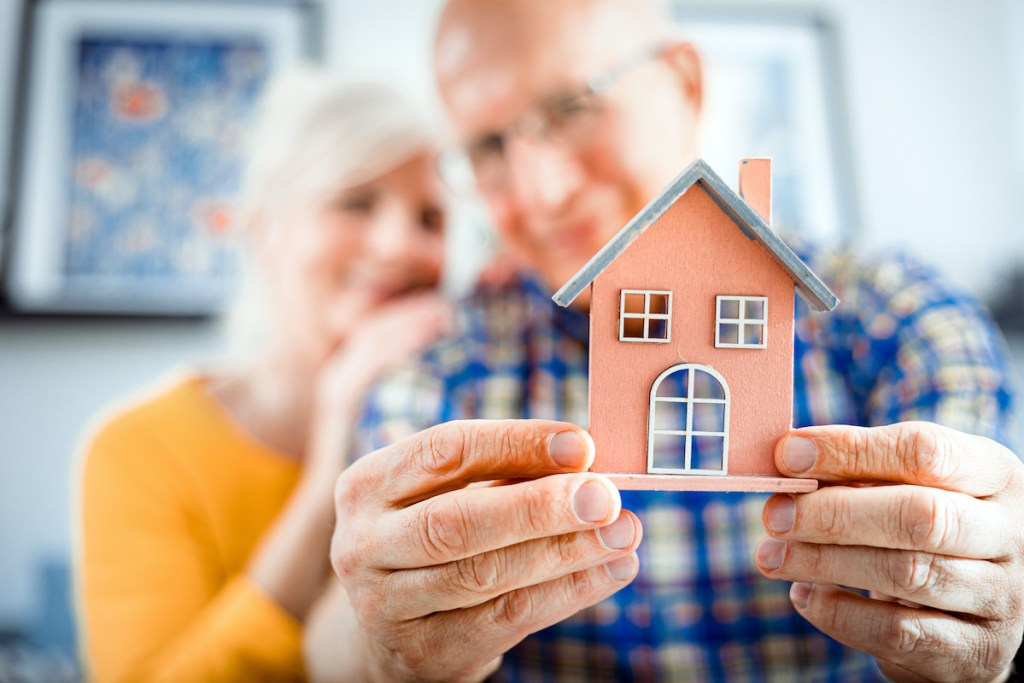 Seniors holding a house figure