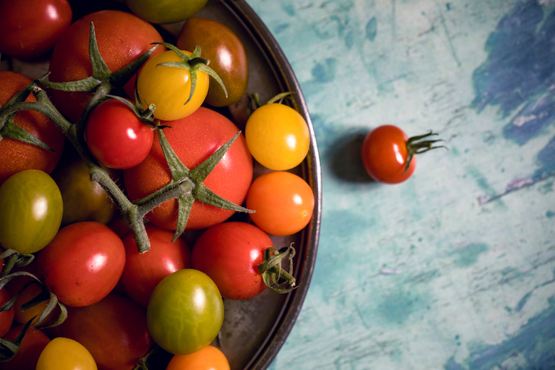Multicoloured tomatoes in a metal bowl