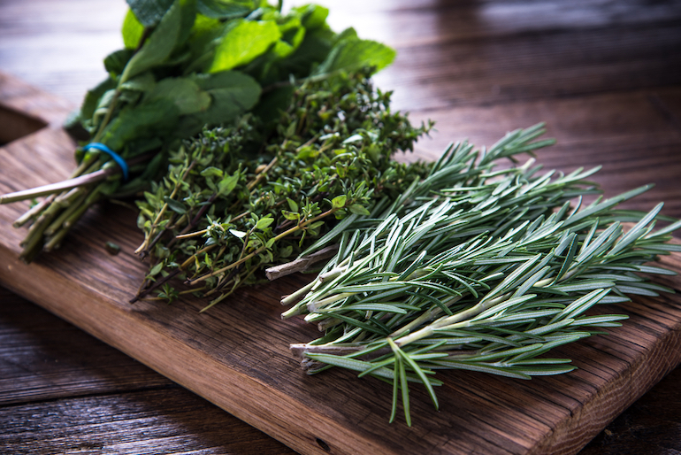 collection of harvested herbs on a brown cutting board