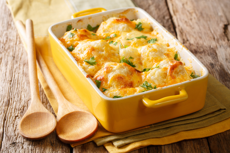 stock image of cauliflower cheese with two wooden spoons