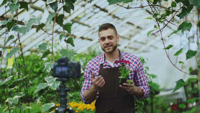 Young male gardening vlogger filming in a greenhouse