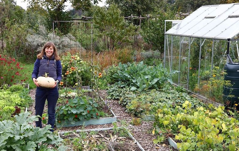 Vera standing in an allotment holding a pumpkin