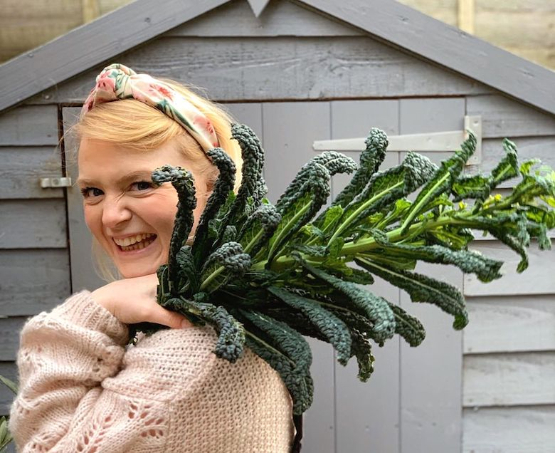 Rachel holding a kale haul and standing in front of a shed