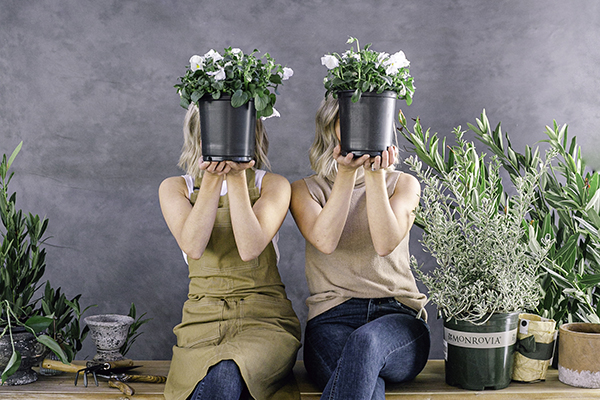Those plant ladies, twin sisters, covering their face with potted flowers