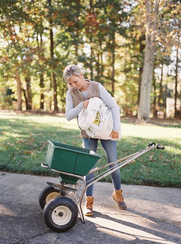 Woman pouring seed into a wheelbarrow outside.