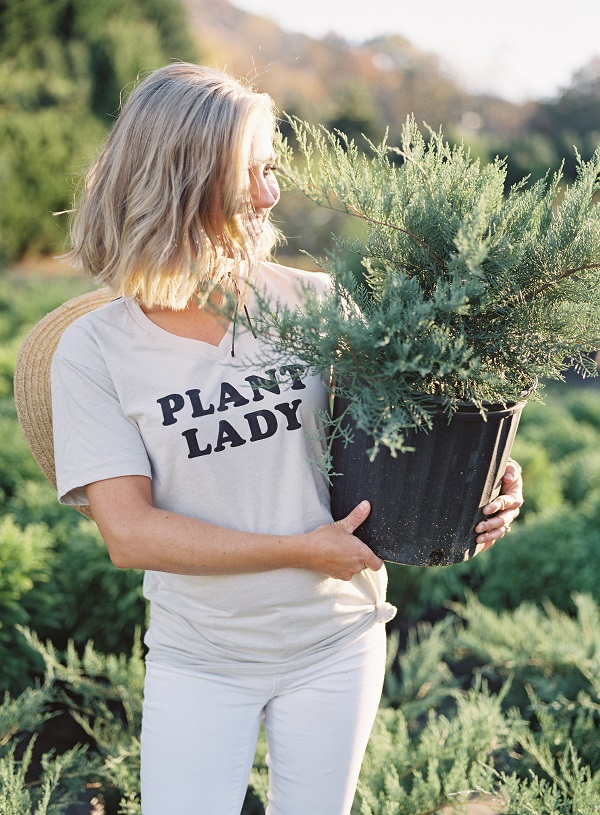 Those Plant Ladies, girl with PLANT LADY shirt and holding a potted shrub