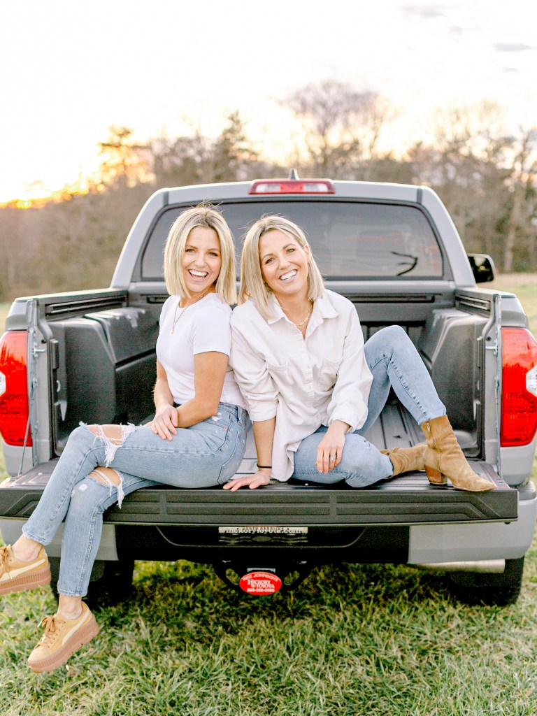 Fawn and Heather of Those Plant Ladies sitting in the bed of their new truck from Mike Johnson's Hickory Toyota.