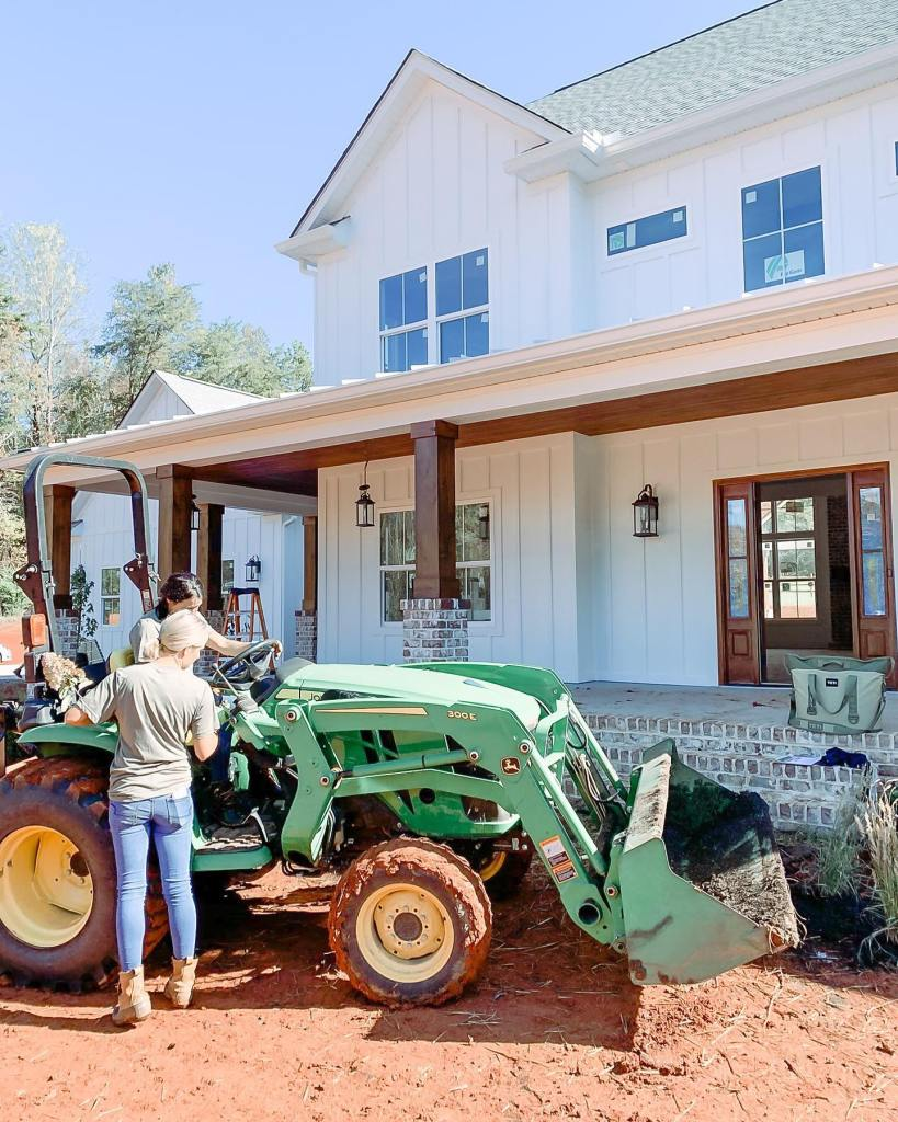 Fawn of Those Plant Ladies teaching a crew member to use the John Deere tractor in front of a white farmhouse.