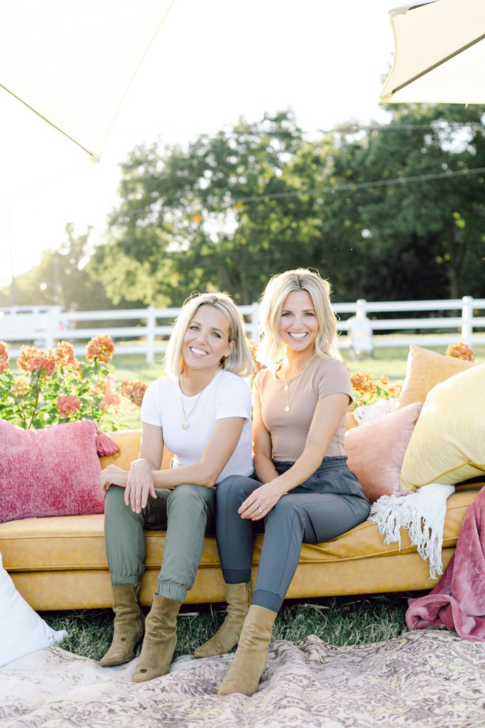 Fawn and Heather of Those Plant Ladies sitting on a sofa, surrounded by pillows and flowers.