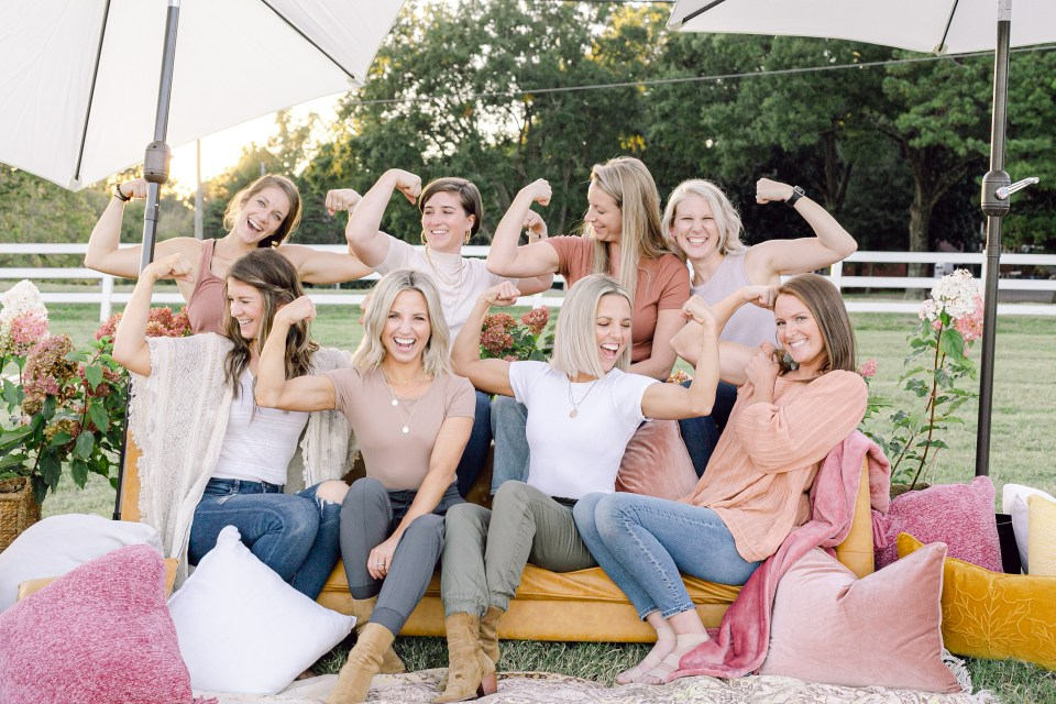 A group of women known as Those Plant Ladies sitting on a sofa outdoors and striking the muscle pose.
