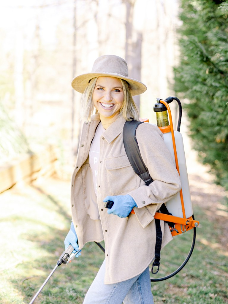 Fawn of Those Plant Ladies using a backpack sprayer to apply pre-emergent to prevent weeds in the grass.