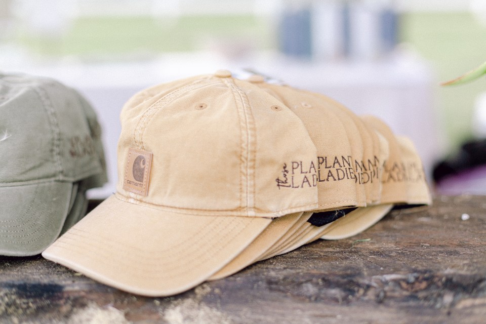 A stack of the official Carhartt hats with the Those Plant Ladies logo on the side.