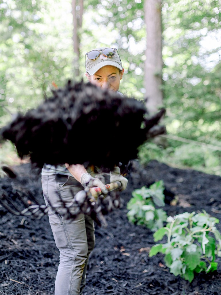 A crew member of Those Plant Ladies shoveling mulch at the landscape installation for The Blooming Estate.