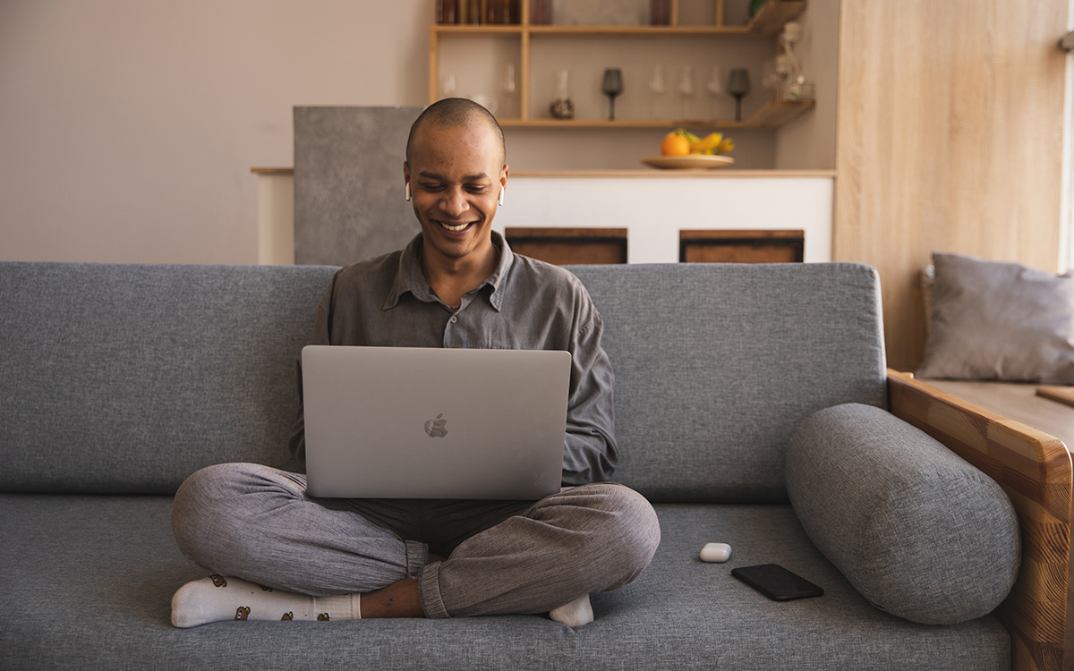 Man sitting cross legged on couch working with computer in lap and smiling