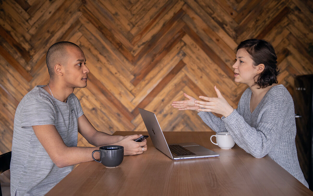 woman and man sitting across the table and engaging in conversation