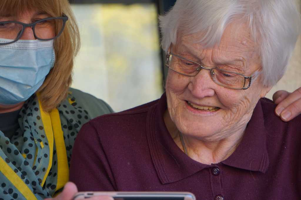 Image shows a person spending time and sharing some content on their mobile phone with an older adult