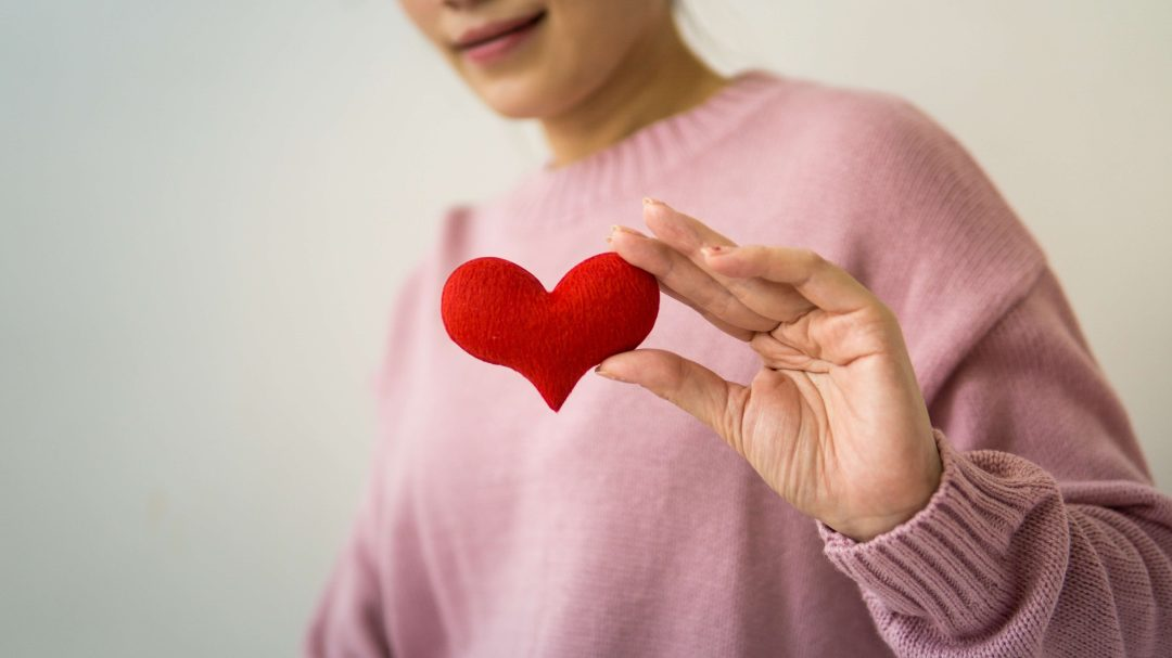 Person in pink sweater holding a picture of heart in their hand
