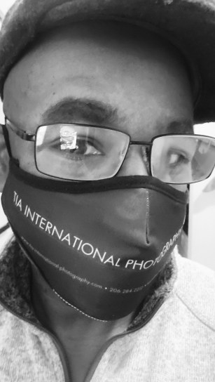 A breathing mask featuring the name, website, and phone number of TIA International Photography as a means of marketing during the pandemic.