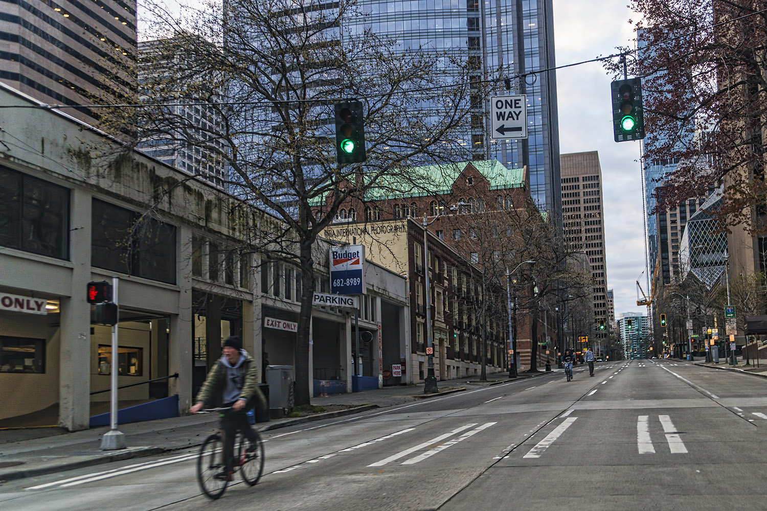 A cyclist and two of his friends proceed along Fourth Avenue in the opposite direction of auto traffic in downtown Seatte. The streets were empty during the mandated citywide quarantine in response to the coronavirus outbreak. (April 2020)