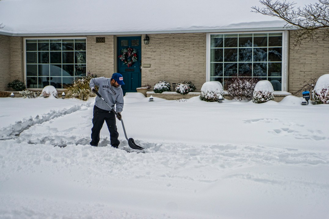A fellow shovels a path through the snow in front of his house. (February 13, 2021)