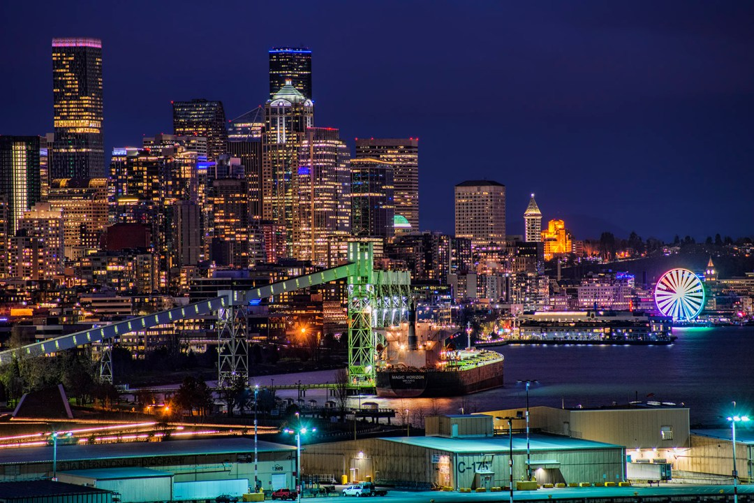 The Seattle Great Wheel (right) is colorfully illuminated alongside its neighboring skyscrapers along Seattle's waterfront. (February 28, 2021)