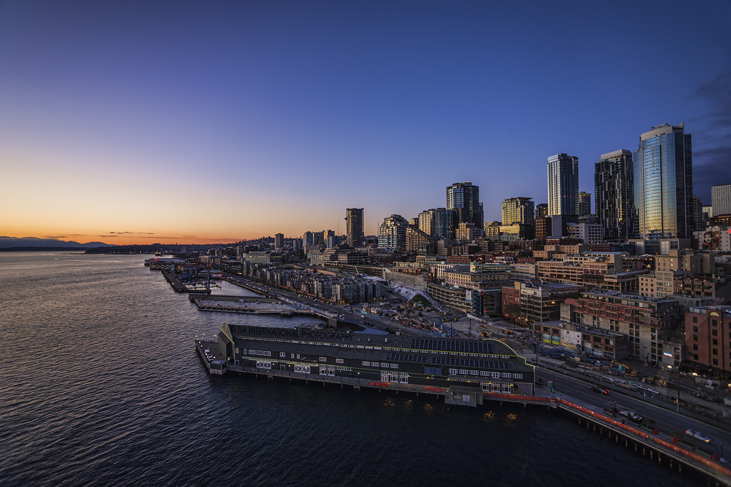 Downtown Seattle & Waterfront from the Great Wheel at sunset. The Seattle Aquarium can be seen in the immediate foreground.