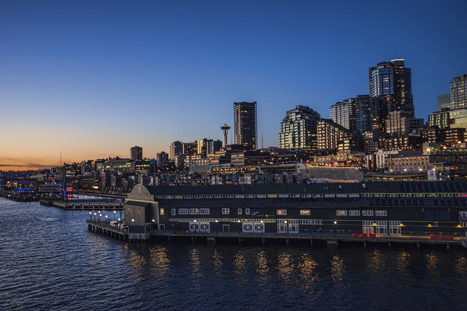 Seattle Waterfront featuring the Seattle Aquarium (foreground) and Space Needle (center) at sunset.