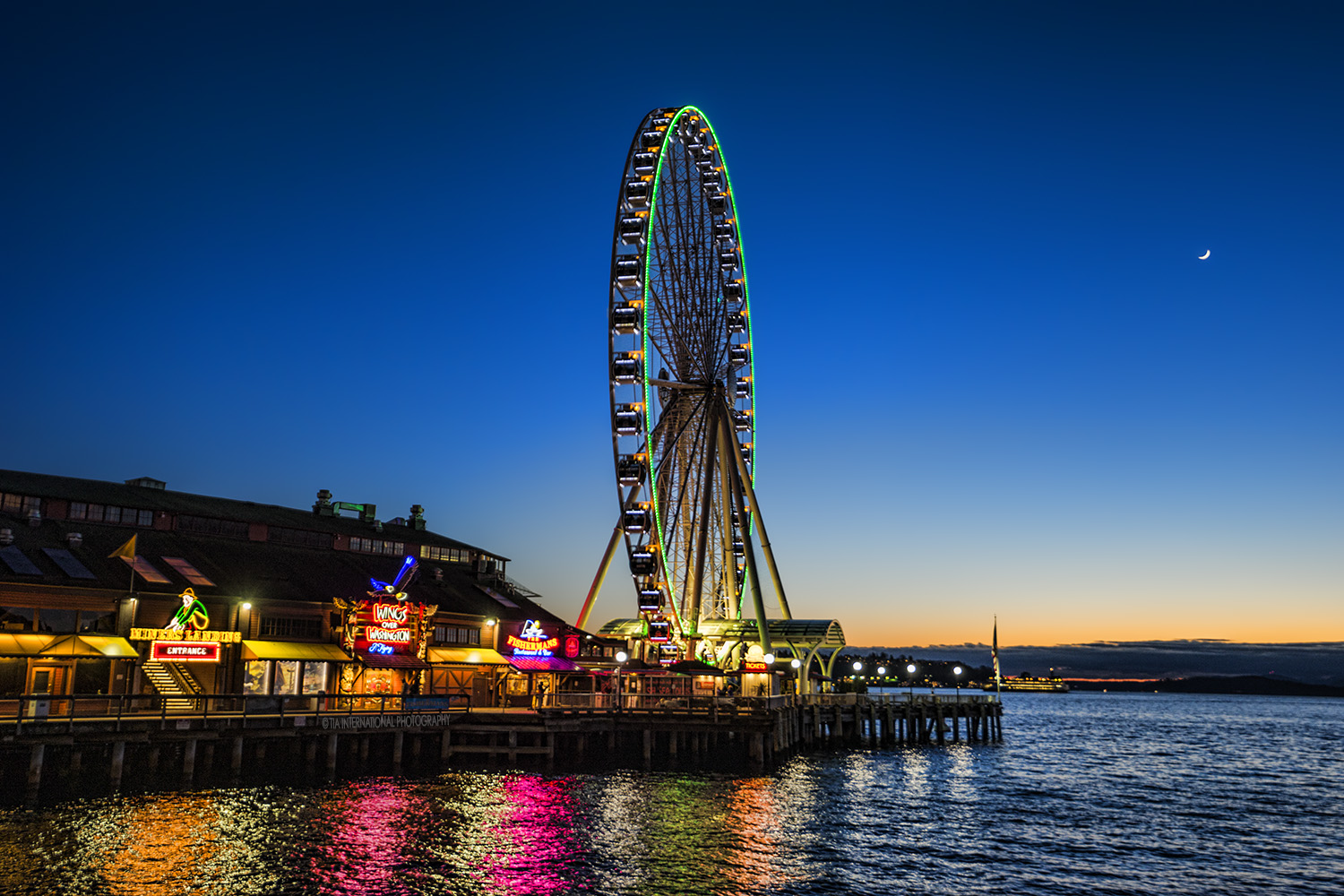 Seattle Great Wheel and Miners Landing tourist attraction at Seattle Waterfront.