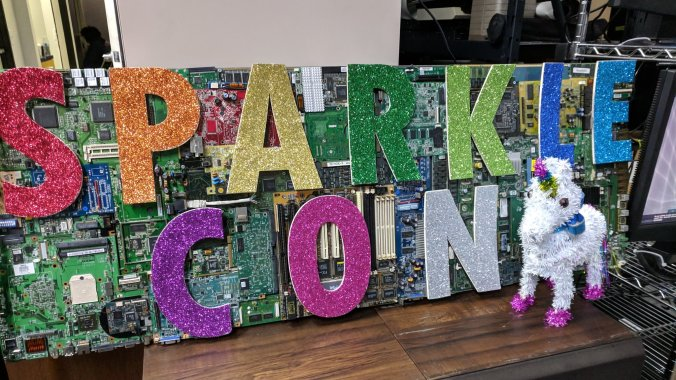 An image of a Sparklecon sign made from colorful, glitter-covered letters glued onto circuit boards. A small unicorn pinata sits to the right of it.