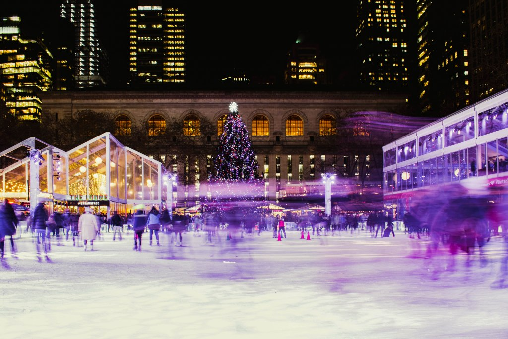 Ice skaters with motion blur make their way around the ice rink at the Bank of America Winter Village in Bryant's Park