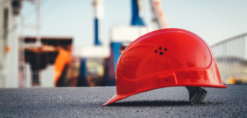 Construction helmet highlighted in front of a construction site.