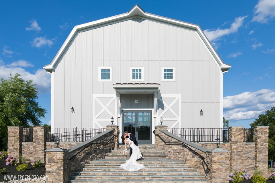 Groom dipping the bride in front of the Rustic Barn at a Rosewood Farms Wedding in Maryland