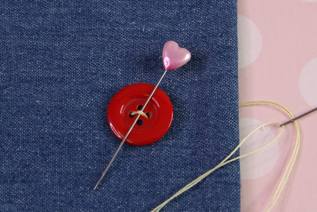 Insert the needle through the underside of the button and up through the button to the right side.