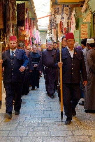 A procession towards the Holy Sepulchre making its presence known in the markets of Jerusalem (Copyright © Tim Stratford 2014)