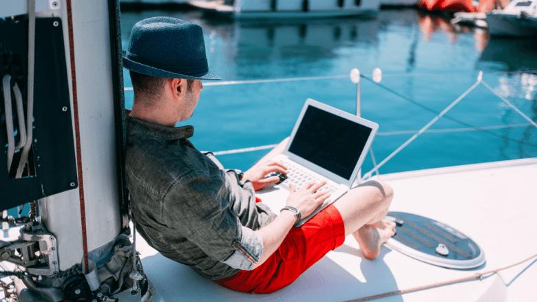 Man op boot aan het werk met een laptop